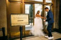 Brautpaar auf dem Weg ins Standesamt New York - Die Braut trägt ein weisses Hochzeitskleid, der Bräutigam blauen Anzug mit weissen Trunschuhen